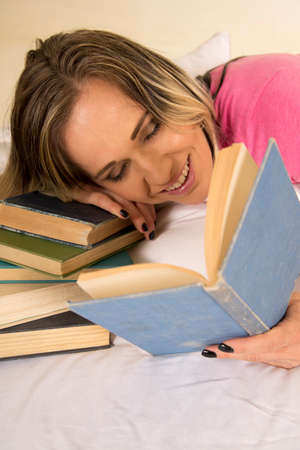 a woman laying on a stack of books, and her pillow with a smile and eyes closed reading her book. Standard-Bild