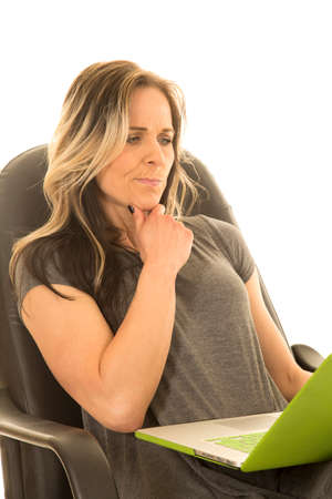 A woman sitting in her office chair, thinking about something on her laptop. photo