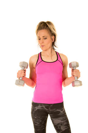 A woman in her fitness gear working out with dumbbells. photo