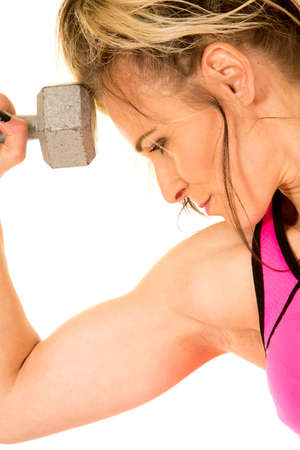A close up of a woman with a dumbbell next to her head, flexing her bicep. photo