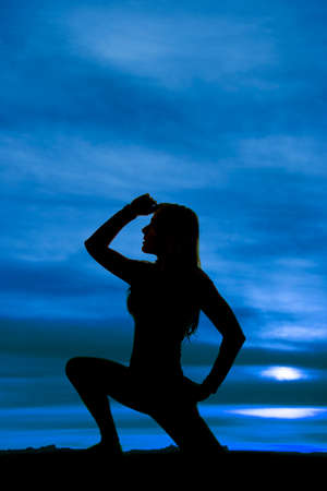 A silhouette of a woman kneeling with  her hand up by her head. photo