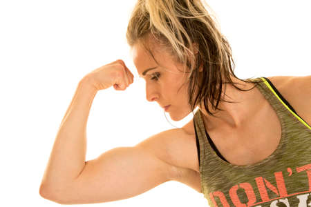 a woman flexing her bicep looking down at her muscle. photo