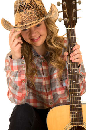 a cowgirl with a big smile holding on to the brim of her hat, with her guitar in her hands. 免版税图像