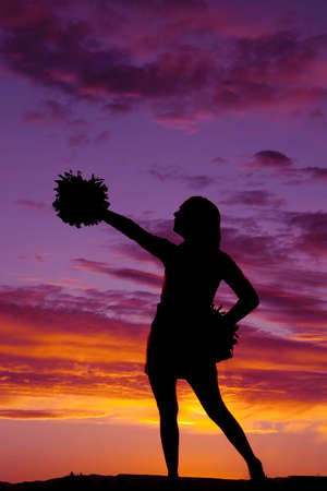a silhouette of a woman in her cheerleader with a pom pom. 免版税图像