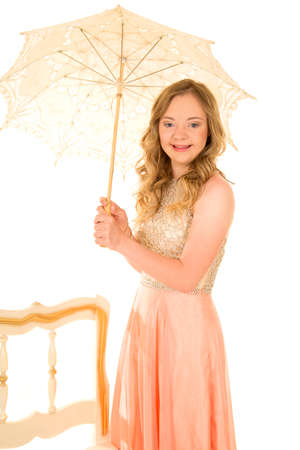 A woman with down syndrome in her peach dress, smiling and holding on to a vintage umbrella.