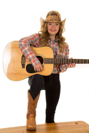a cowgirl with down syndrome with a big smile playing her guitar.