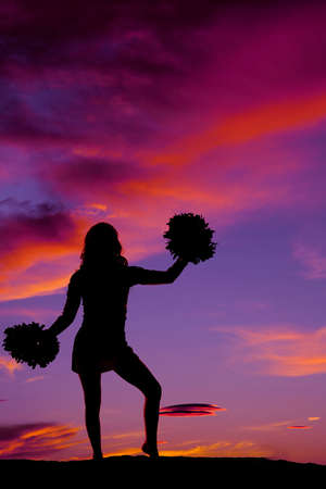 A silhouette of a woman cheerleader with her pom poms in the outdoors. 免版税图像