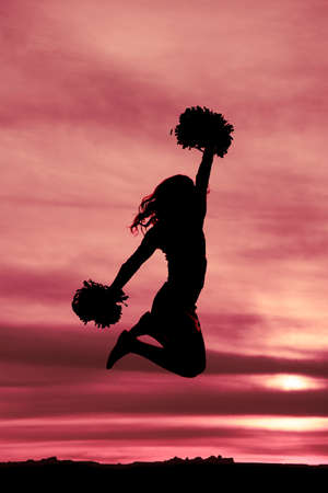 a silhouette of a cheerleader with her pom poms jumping into the air.