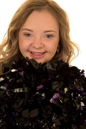 a close up of a cheerleader with her pom poms up by her face, she has down syndrome.