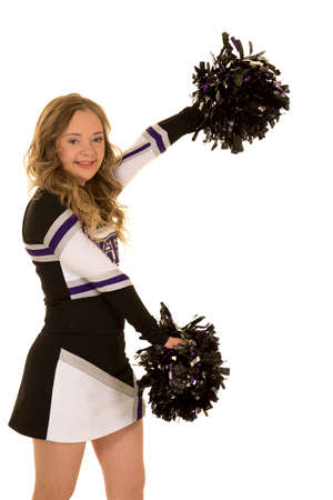 A teen with down syndrome in her cheerleading uniform smiling and posing.