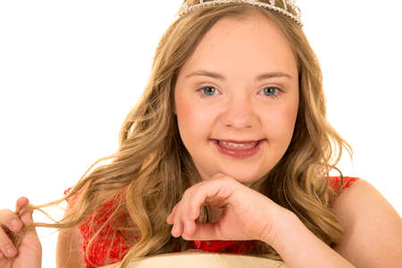 A teen in her red dress and crown with a smile the teen has down syndrome.