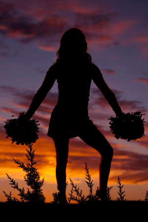 A silhouette of a cheerleader with her pom poms standing in the outdoors.