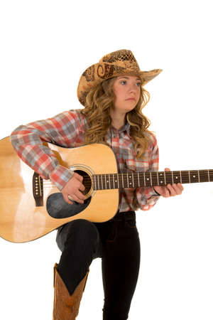 a cowgirl with down syndrome holding on to her guitar with a serious expression on her face.