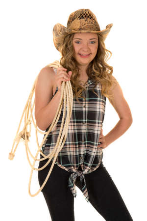 a cowgirl with down syndrome with a big smile holding on to her rope wearing her cowgirl hat.
