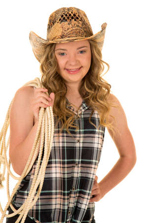 a woman with down syndrome in her western cowgirl hat holding on to a rope with a smile.