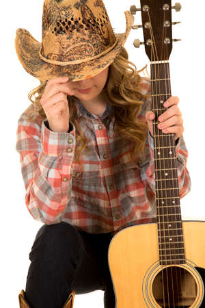 a cowgirl holding on to her guitar with her eyes covered.