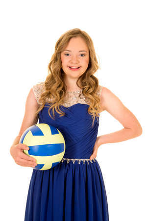 a woman with down syndrome in her fancy dress with a volleyball. 免版税图像
