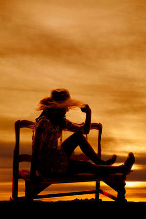 A silhouette of a woman sitting on a bench watching the sunset in the sky.
