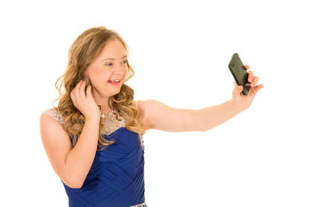 A woman with down syndrome holding out her phone taking a picture, wtih a big smile