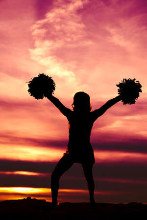 a silhouette of a cheerleader standing up with her pom poms in her hands, high v shape.