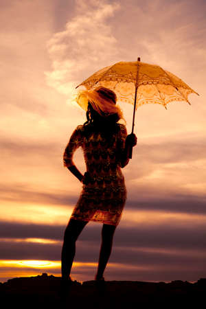 A silhouette of a woman with her umbrella in her dress in the outdoors. 免版税图像