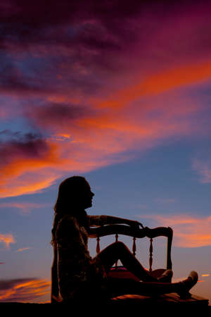 A silhouette of a woman sitting on a bench enjoying the beauty of nature.