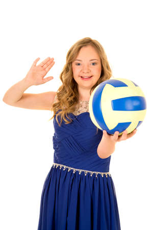 A woman with down syndrome in her fancy dress with a volleyball, and smile.
