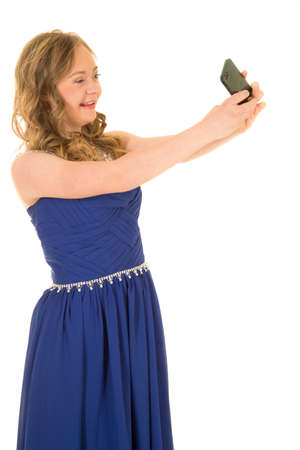 a woman with down syndrome in a fancy blue dress holding on to her phone to take a picture of her. 免版税图像
