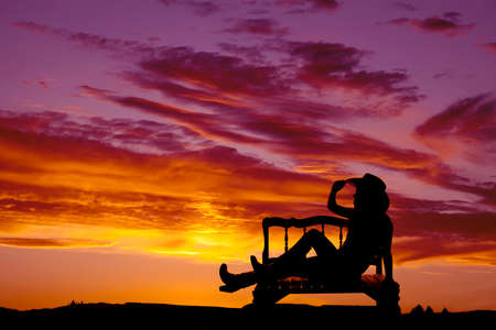 a silhouette of a cowgirl sitting on a bench with a beautiful sky behind her. 免版税图像