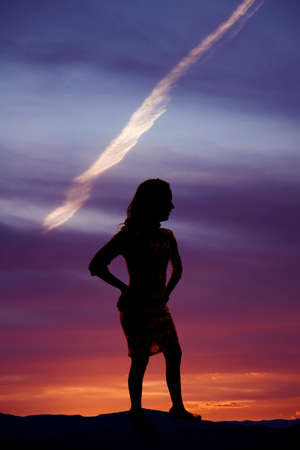 a silhouette of a woman standing in the night, enjoying the sky.