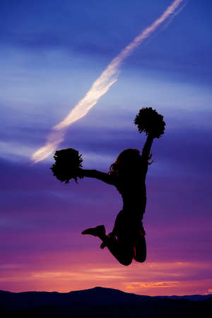 A silhouette of a cheerleader jumping into the air, with her pom poms.