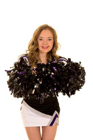 Een cheerleader met het syndroom van Down met een grote glimlach op haar gezicht, die op haar pom poms. Stockfoto