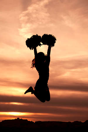 A silhouette of a cheerleader with her pom poms jumping in the air. 免版税图像