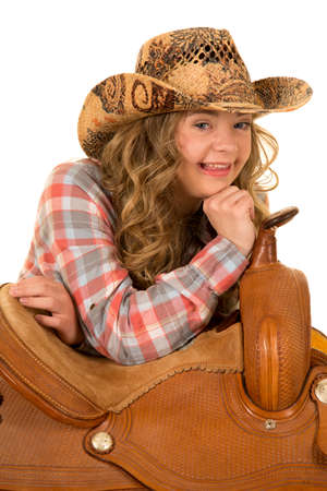 challenged: A cowgirl with down syndrome with a big smile laying on a saddle. Stock Photo