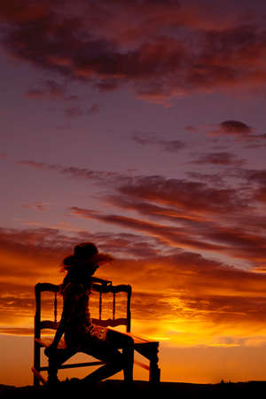 A silhouette of woman sitting on a bench with a beautiful sunset.