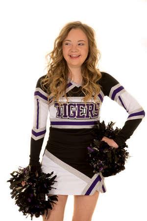 une cheerleader avec le syndrome de Down regardant sur le côté avec un sourire sur son visage.
