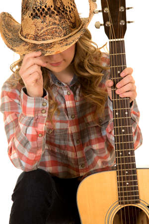 a cowgirl hiding her face, holding onto her guitar.