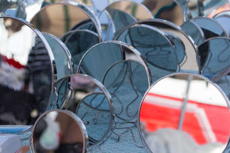multitude: a multitude of mirrors posing in a market Stock Photo