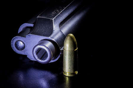full jacket bullet: Black gun and bullets on a black background.