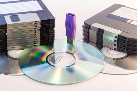 rom: Progression of computer data storage media from floppy to USB flash stick through the DVD rom Stock Photo