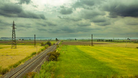 extending: A horizontal shot of railroad tracks extending to the horizon on a cloudy day Stock Photo