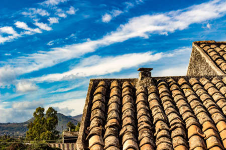 residential construction: The ancient roof on a blue sky with clouds streaked