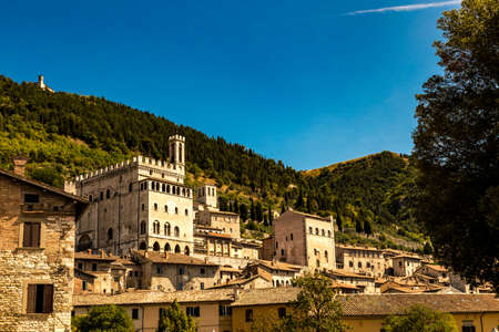 Italy: view of the ducal palace of Gubbio. In the background the wooded forest of Mount Ingino Editorial