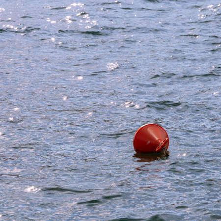 The red buoy floating in the middle of the sea