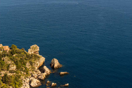 Aerial view of Isola Bella's island and beach on blue ocean water in Taormina - Sicily.