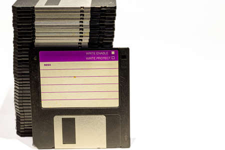 numerous black floppydisks lined up on a white background