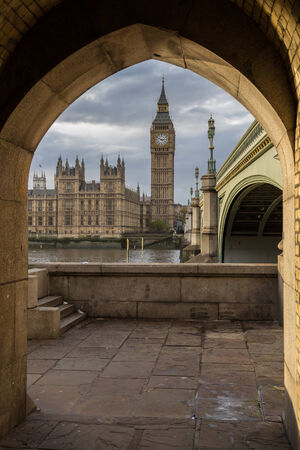 unusual angle: Photograph of big ben  the famous London landmark from an unusual angle, framed by a stone arch