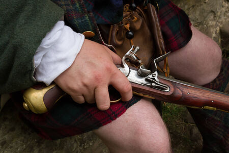 dueling pistol: Close up of a flintlock pistol being held naturally resting on knee of a jacobite wearing a kilt