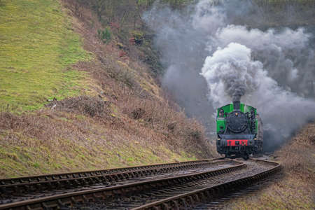 exiting: Steam train, locomotive smoking exiting tunnel. TKh 2944 was made in Poland Editorial