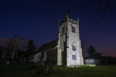haunting: Country church tower lit up at night with a starry sky and haunting grave stones